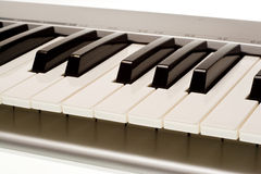 Midi keyboard. Side view of a midi keyboard isolated on white Royalty Free Stock Images