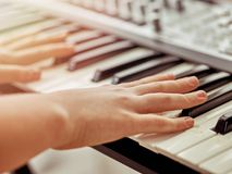 Midi keyboard or electronic piano and playing child hands. stock photos