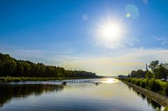 Midi sur le canal de aviron les bateaux pr?parent pour d?marrer, l'eau lisse, ciel bleu, beau photo libre de droits