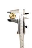 Midiendo el diámetro de la moneda de cobre metal el calibrador Imágenes de archivo libres de regalías
