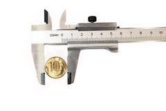 Midiendo el diámetro de la moneda de cobre metal el calibrador Imagen de archivo