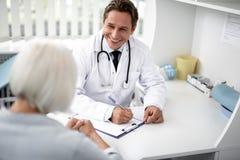 Midja upp av den gladlynta praktiker som ler till patienten, medan arbeta royaltyfria bilder