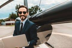Midja upp av den skäggiga affärsmannen som ler, medan stå med hans bärbar dator royaltyfria foton