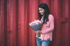Midja upp av den unga kvinnan som ler och ser blommorna royaltyfri foto