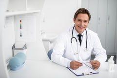 Midja upp av den vänliga doktorn som ler, medan vara på arbete royaltyfri bild