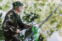 Midja upp av en pensionerad sportfiskare som fiskar på helgen arkivbild