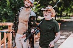 Midja upp av en positiv äldre sportfiskare med hans son royaltyfria foton
