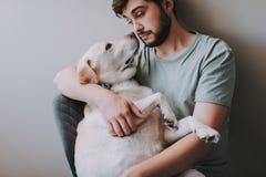 Midja upp av en ung man som sitter i stolen med hans hund royaltyfri bild