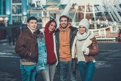 Midja upp av fyra vänner i utomhus- kläder som står och ler arkivbilder