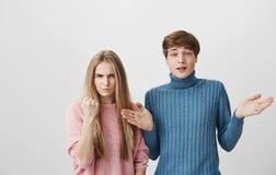 Midja-uppskott av caucasian par Den blonda mannen i blå tröja ser kameran med förvirring, rycker på axlarna skuldror Fotografering för Bildbyråer