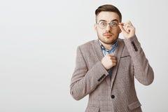 Midja-uppskottet av den gulliga blyga och otrygga manliga nerden i exponeringsglas och hållande näve för utsmyckat omslag nära fö arkivfoton