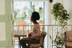 Midjan av afrikanska kvinnan som den har, vilar upp i kafé royaltyfri fotografi