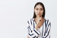 Midjasom skjutas av trendig attraktiv kvinnlig coworker, i randig blus, vikande kanter och att säga shhh stundframställning fotografering för bildbyråer