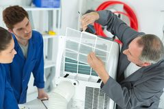 Midle age conditioning technician with students. Air-conditioning stock photos
