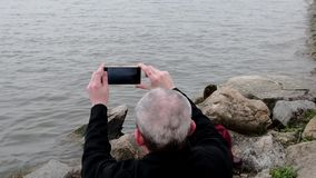 Midle aged man sitting on the shore of the lake. Solitude mature man recording video by mobile phone on the bank