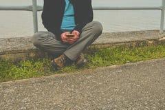 Midle a vieilli l'homme s'asseyant sur le rivage du lac Homme mûr de solitude à l'aide du téléphone portable sur la banque Concep Images stock
