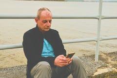 Midle a vieilli l'homme s'asseyant sur le rivage du lac Homme mûr de solitude à l'aide du téléphone portable sur la banque Concep Photo stock