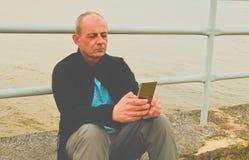 Midle a vieilli l'homme s'asseyant sur le rivage du lac Homme mûr de solitude à l'aide du téléphone portable sur la banque Concep Image libre de droits