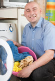 Midlle-aged man doing laundry Stock Images