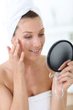 Midlle-aged woman applying cream on her face Stock Photography