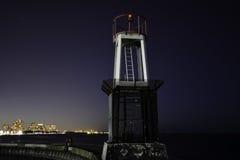 Midnatt himmel med stjärnor och ljus i bakgrunden på en hamnpir med fyren royaltyfri fotografi