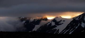 midnight berg över den snöig sunen arkivbild