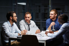 Midnight briefing. Group of businessmen having late discussion in office royalty free stock photos
