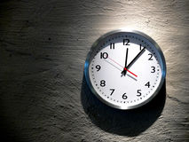 Midnight Clock. An analog clock hanging on a solid stone wall Stock Image