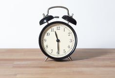 It is almost midnight or noon. It is 11:30 o`clock. The time is 11:30 am or pm. half past eleven. A retro clock isolated on a wooden table and white background Royalty Free Stock Photos