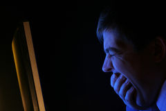 Midnight in the office. A man yawns in front of a flat screen computer monitor Royalty Free Stock Images