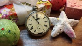 Midnight on the old clock among the Christmas gifts on wooden table Stock Photo