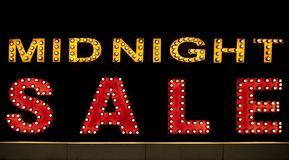 Midnight sale background. Brightly colored vintage advertising sign board with illumination. Lamps stock image
