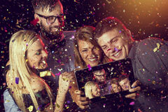 Midnight selfie. Two young couples taking a selfie at midnight on a New Year's Eve party Royalty Free Stock Image
