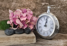 Midnight soon on a clock. Retro clock at twelve soon with flowers on old book on wooden background royalty free stock photography