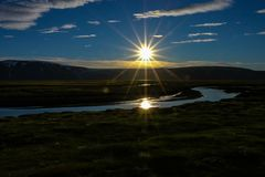Midnight sun in the arctic. A beautiful and dreamy scenery of the midnight sun over the glacier Langjokull in the highland of Iceland, mystic reflection in the stock photo