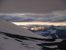 Midnight sun over the snowy mountains Stock Photo