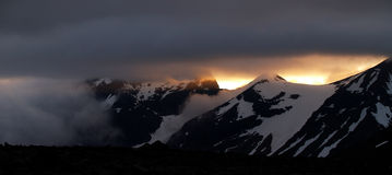 Midnight sun over the snowy mountains Stock Photography