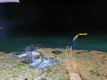 Midnight swim. Colormix, water, land, boat, dark, shoreline royalty free stock images