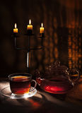 Midnight tea. Tea by candlelight with a reflection of the flames of the burning hearth Royalty Free Stock Photography