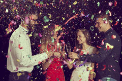 Midnight toast. Four young people on a New Year's eve party making a toast at midnight royalty free stock photography
