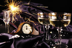 Midnight toast for the New Year. Champagne glasses with clock and fireworks royalty free stock photos