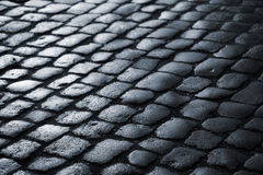 Midnight in town. Wet cobblestone at nighttime - Denmark. Very shallow DOF Royalty Free Stock Image