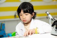 Miúdo asiático que senta-se pelo microscópio Foto de Stock Royalty Free