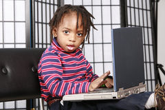 Miúdo bonito com seu computador Fotografia de Stock Royalty Free