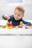 Miúdo bonito que joga no assoalho em casa Fotos de Stock Royalty Free