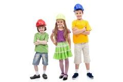 Miúdos com levantamento protetor dos capacetes Fotografia de Stock