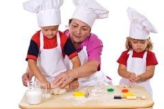 Miúdos de ensino da avó como fazer bolinhos Fotografia de Stock Royalty Free