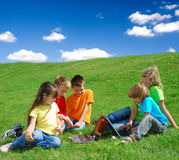 Miúdos em um prado com portáteis Imagem de Stock