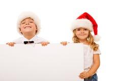 Miúdos felizes com chapéus de Santa e cartão branco Foto de Stock Royalty Free