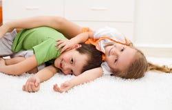 Miúdos felizes que wrestling em seu quarto Fotos de Stock Royalty Free